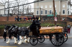 Another shot of Marion Barry 's casket as it pulls past a group of children. As the carriage approached the children flocked to the fence to get a last look at the Mayor